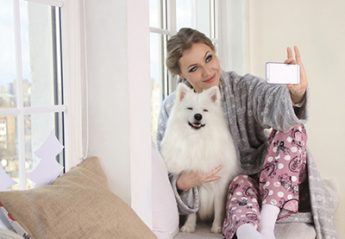 A woman taking a selfie with a dog