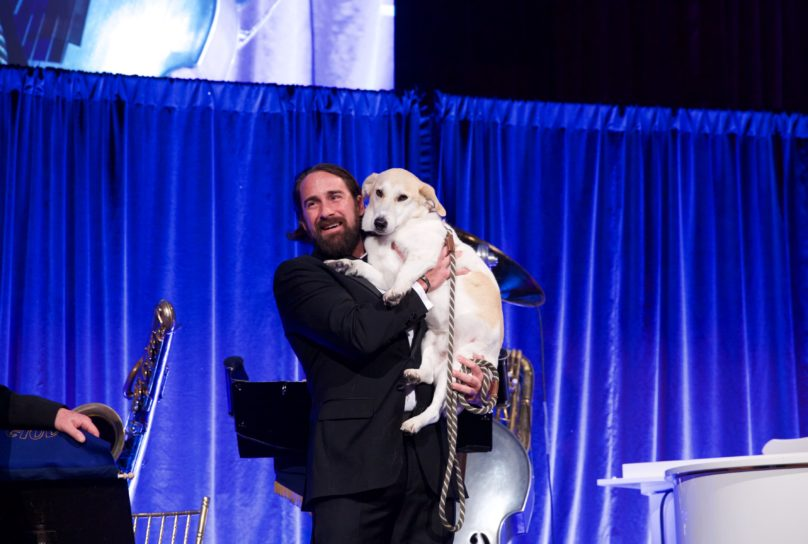 A man holds a dog onstage at AMC's 2018 Top Dog Gala