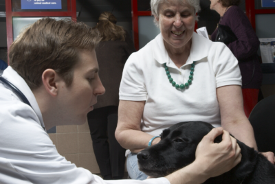A client and veterinarian pet a seeing eye dog in the Animal Medical Center's waiting room