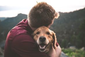 A man hugs a dog on top of a mountain