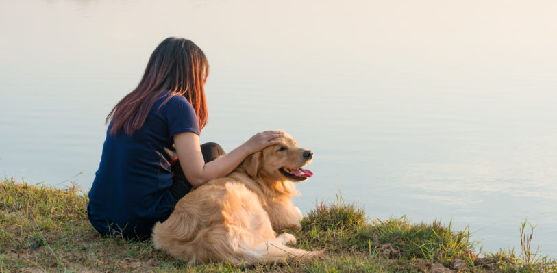Woman with dog overlooking water