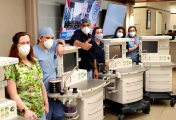 A team of veterinarians wearing masks stands around four ventilators