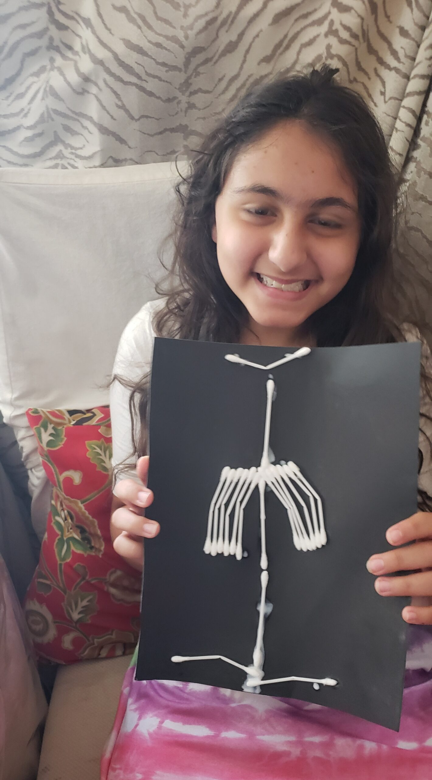 Child posing with x-ray made using household craft materials