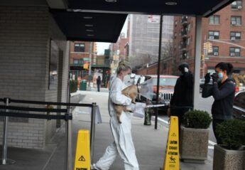 A pet owner picks up her dog from AMC's curbside pick-up service