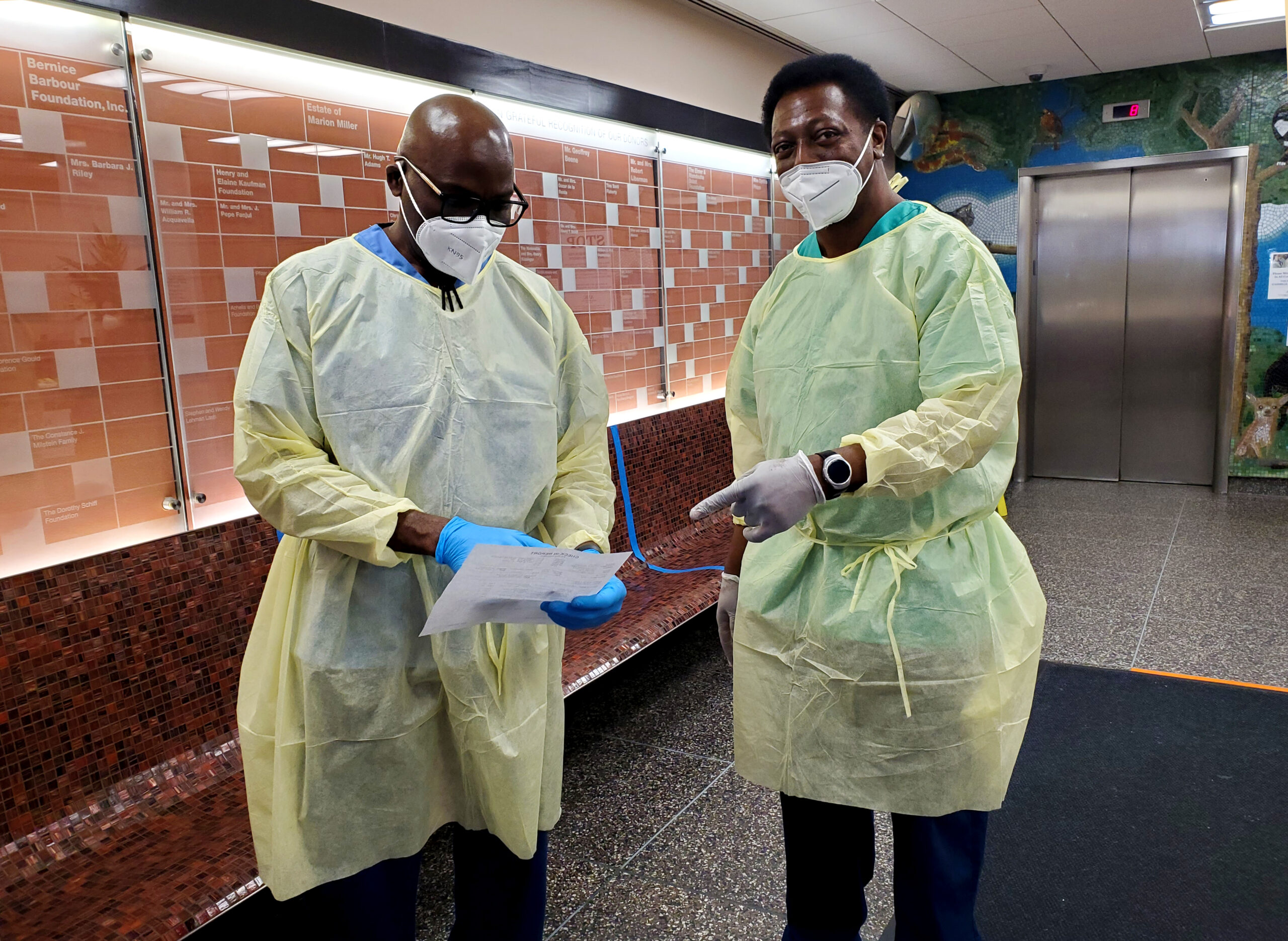 Two masked veterinary professionals stand in the lobby of the Animal Medical Center of New York City