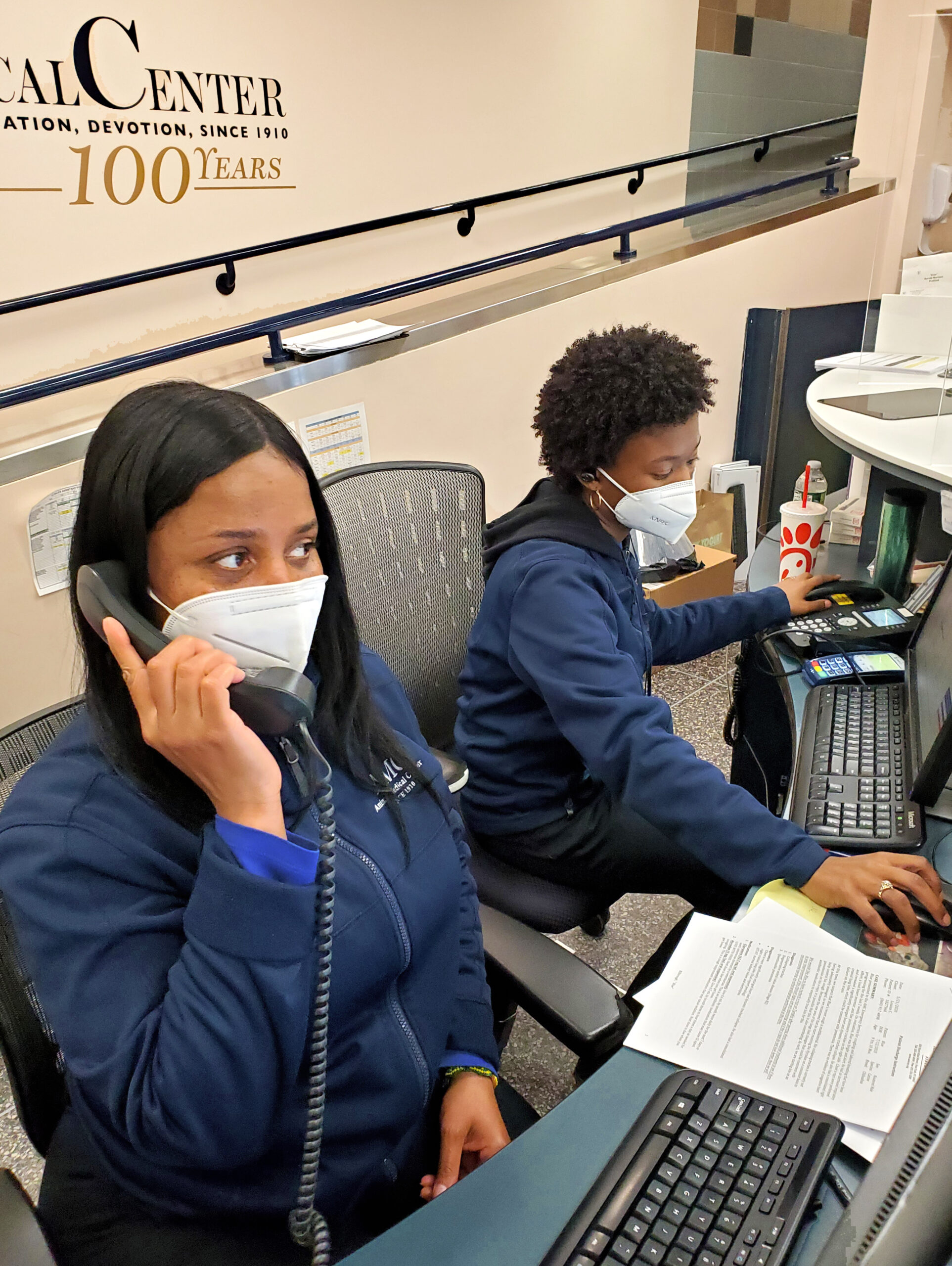 Two masked client services professionals at the Animal Medical Center of New York City