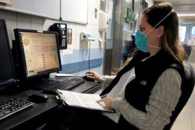 A veterinary professional on the phone while wearing a mask