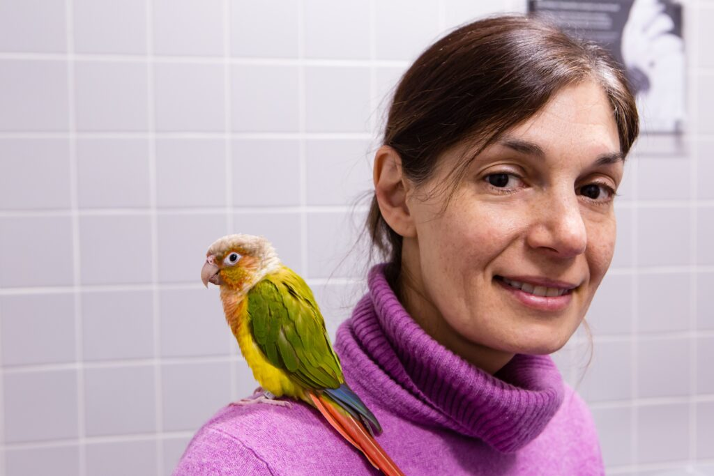 A woman with a pet bird on her shoulder